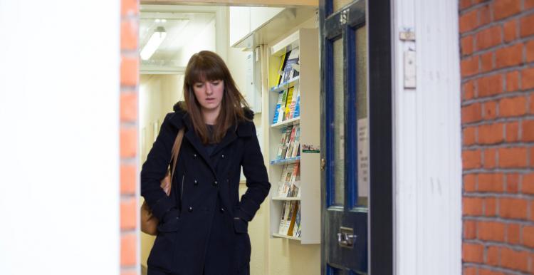 A lady walking by a door
