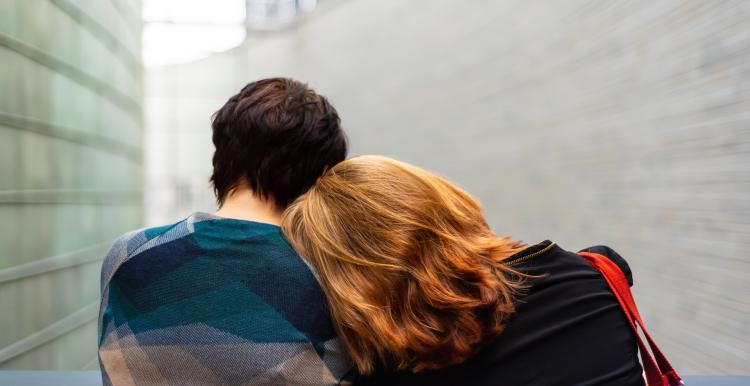 two people sitting close together leaning on each other