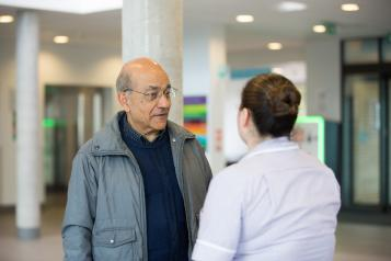 Older Asian man talking to a nurse