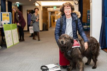 Lady in blue jacket with a brown hearing dog
