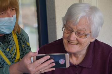 Older lady smiling at her mobile phone