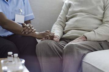 A nurse holding an old man's hand on the sofa.