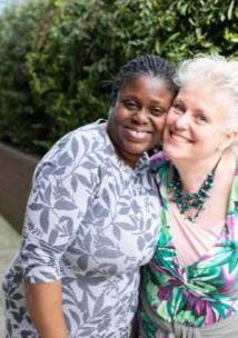 two middle aged woman hugging each other